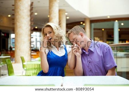 Portrait of a happy young couple looking away while sitting near a table at mall and planning purchases