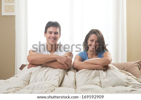 Portrait of a happy young couple lying on bed - stock photo