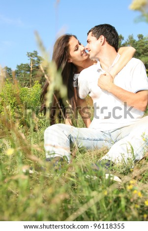 Portrait of a happy young couple sitting on grass in a park - Outdoor - stock photo