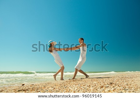 Portrait of a happy young couple twirling on the beach. Couple enjoying a summer vacation. - stock photo