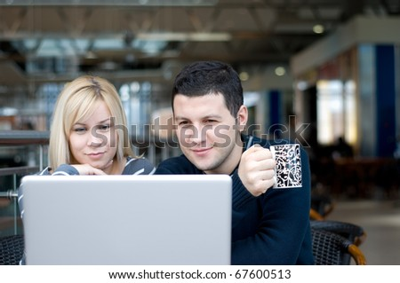 Portrait of a happy young couple using laptop - stock photo