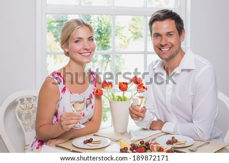 Portrait of a happy young couple with wine glasses having food at home - stock photo