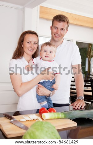 Portrait of a happy young family at home in the kitchen - stock photo