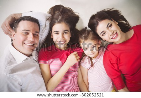 Portrait of a happy young family with kids lying on a floor at home - stock photo