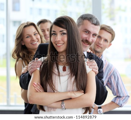 Portrait of a happy young female business leader standing in front of her team