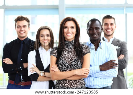 Portrait of a happy young female business leader standing in front of her team - stock photo