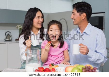 Portrait of a happy young girl enjoying breakfast with parents in the house