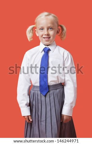 Portrait of a happy young girl in school uniform over orange background - stock photo