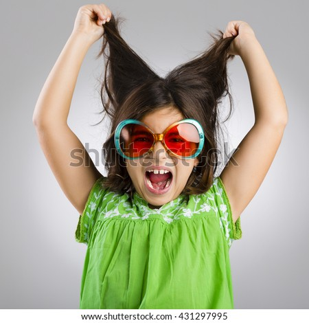 Portrait of a happy young girl wearing funny sunglasses - stock photo