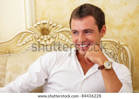 Portrait of a Happy young guy sitting on the classic sofa - stock photo