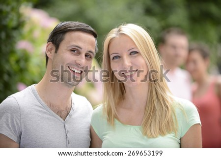 Portrait of a happy young heterosexual couple looking at camera - stock photo