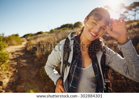Portrait of a happy young hiker woman in nature. Young caucasian woman wearing sunglasses looking at camera with a backpack on a summer day. Eco tourism and freedom concept - stock photo