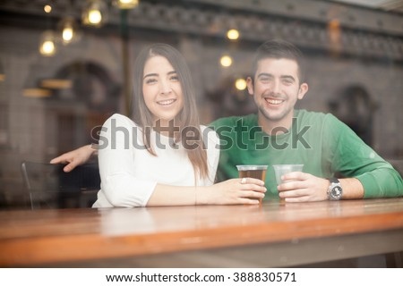Portrait of a happy young Hispanic couple having fun and drinking beer at a bar