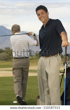 Portrait of a happy young male golfer with man playing in background - stock photo