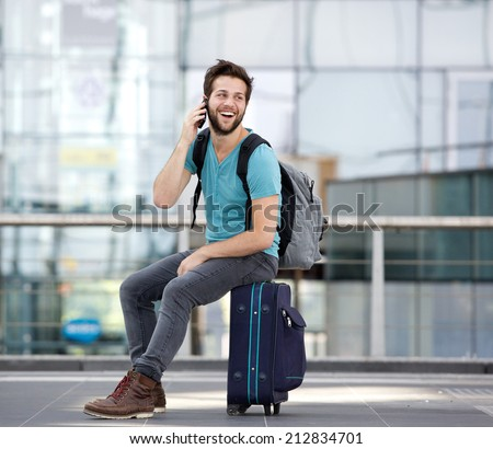 Portrait of a happy young man calling by mobile phone at airport - stock photo