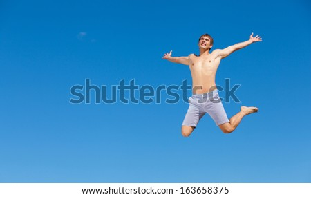Portrait of a happy young man having fun on the beach on a summer vacation. - stock photo