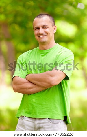 Portrait of a happy young man in a forest - stock photo