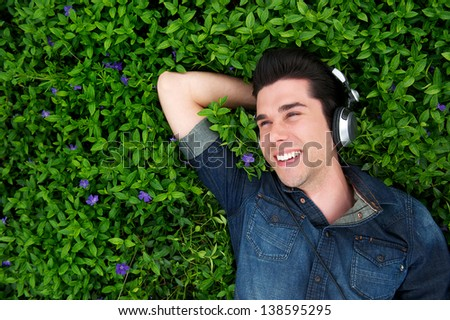 Portrait of a happy young man lying on grass, listening to music with headphones - above view - stock photo