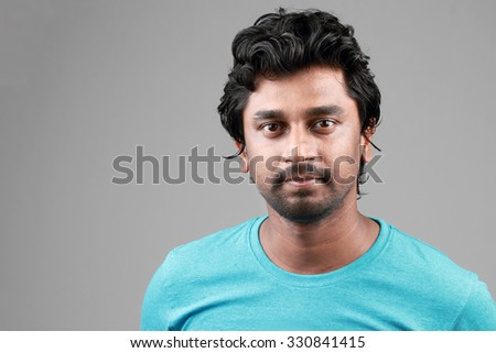 Portrait of a happy young man of Indian origin - stock photo