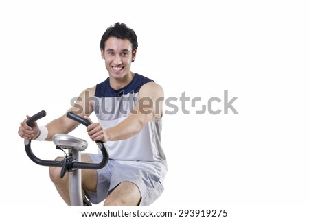 Portrait of a happy young man on exercise bike over white background - stock photo