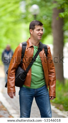 Portrait of a happy young man outdoor in a forest - stock photo
