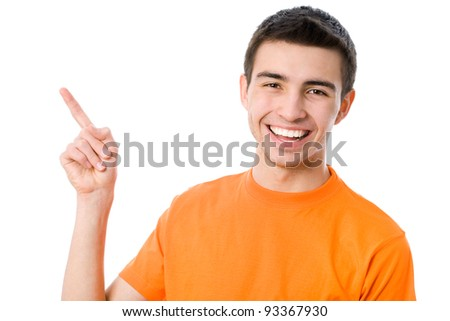 Portrait of a happy young man pointing at something interesting over white background - stock photo