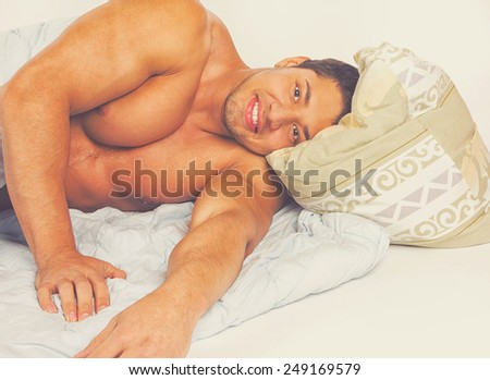 Portrait of a happy young man relaxing on bed at home - stock photo