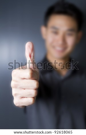Portrait of a happy young man showing good job sign. - stock photo