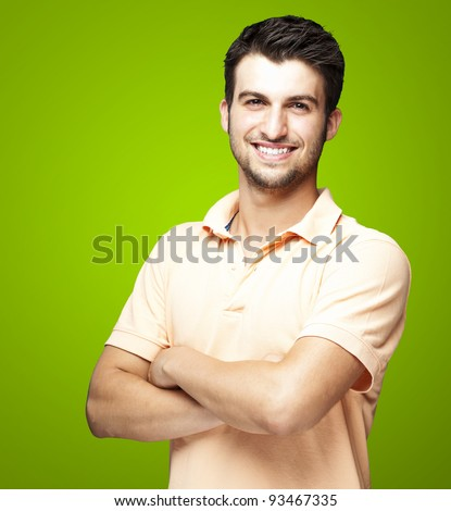 portrait of a happy young man smiling against a green background