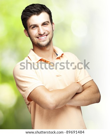 portrait of a happy young man smiling against a nature background - stock photo
