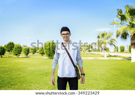 Portrait of a happy young man standing outdoors with small bag. - stock photo