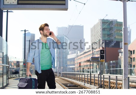 Portrait of a happy young man talking on mobile phone at train station platform - stock photo