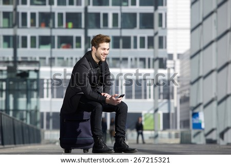 Portrait of a happy young man waiting at station with mobile phone - stock photo