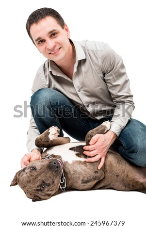 Portrait of a happy young man with a pitbull puppy - stock photo