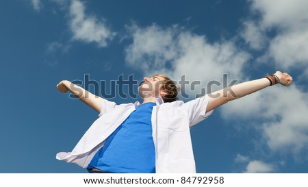 portrait of a happy young man with arms outstretched against sky - stock photo