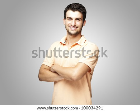portrait of a happy young man with crossed arms against a grey background