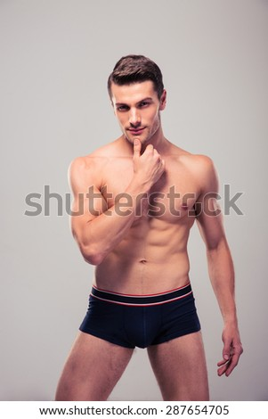 Portrait of a happy young man with muscular body standing over gray background and looking at camera - stock photo