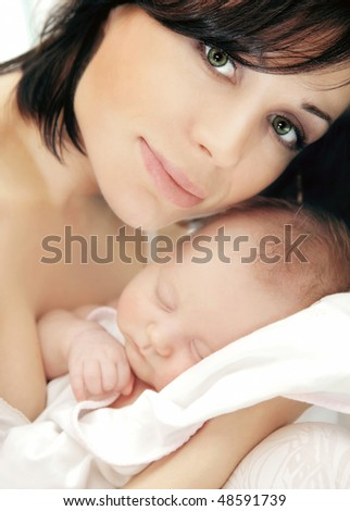 Portrait of a happy young mother holding a baby - stock photo
