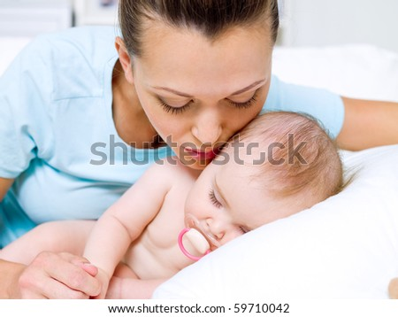 Portrait of a happy young mother near sleeping baby - stock photo