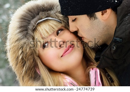 portrait of a happy young romantic couple in winter park
