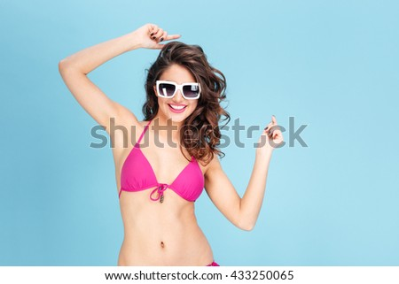 Portrait of a happy young smiling woman wearing sunglasses and bikini isolated on the blue background - stock photo