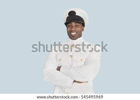 Portrait of a happy young US Navy officer with arms crossed over light blue background