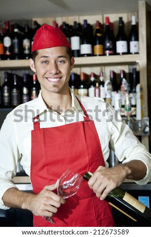 Portrait of a happy young waiter with bottle and glass