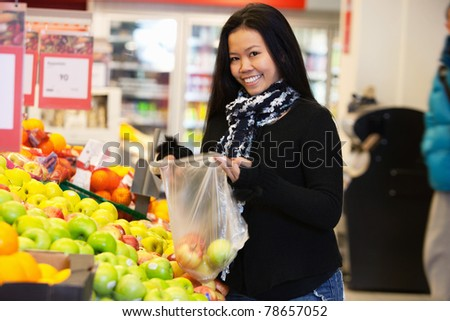 Portrait of a happy young woman buying apple in the supermarket - stock photo
