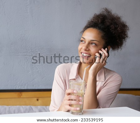 Portrait of a happy young woman calling by mobile phone - stock photo