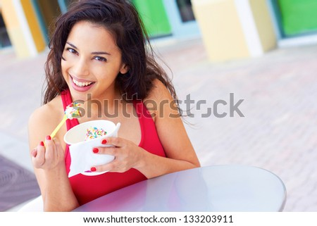 Portrait of a happy young woman enjoying frozen yogurt at cafe table. Horizontal shot. - stock photo