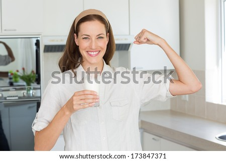 Portrait of a happy young woman flexing muscles while drinking water in the kitchen at home - stock photo