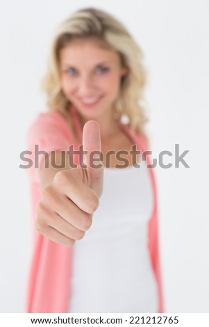 Portrait of a happy young woman gesturing thumbs up over white background - stock photo