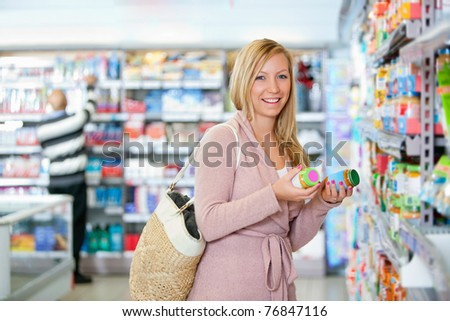 Portrait of a happy young woman holding jar in the supermarket - stock photo