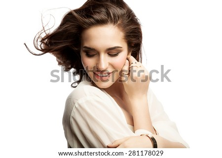 Portrait of a happy young woman in a light blouse and with  flowing hair on a white background isolated - stock photo